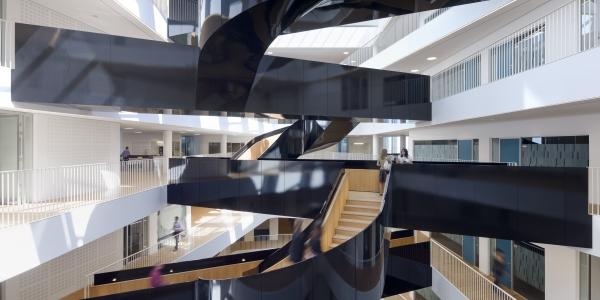 En skulpturel, sortlakeret trappe, der binder etagerne sammen